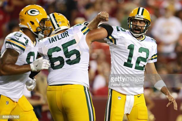 Quarterback Aaron Rodgers of the Green Bay Packers celebrates a touchdown pass with teammate Lane Taylor against the Washington Redskins in the first...