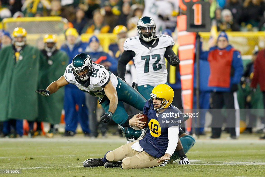 Quarterback Aaron Rodgers #12 of the Green Bay Packers controls the ball against Cedric Thornton #72 and Mychal Kendricks #95 of the Philadelphia Eagles during the game at Lambeau Field on November 16, 2014 in Green Bay, Wisconsin.