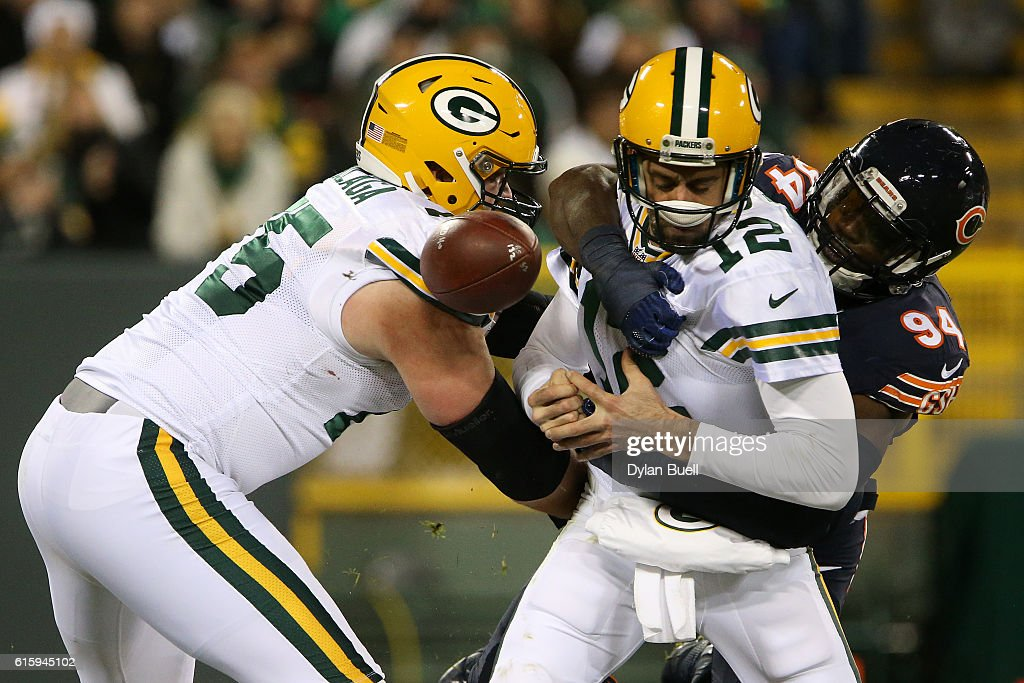 Quarterback Aaron Rodgers #12 of the Green Bay Packers fumbles the ball for outside linebacker Leonard Floyd #94 of the Chicago Bears to recover the ball for a touchdown in the third quarter at Lambeau Field on October 20, 2016 in Green Bay, Wisconsin.