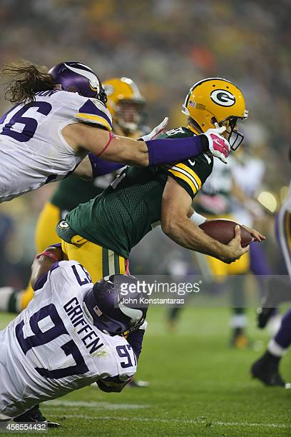 Quarterback Aaron Rodgers of the Green Bay Packers is sacked by Brian Robison and Everson Griffen of the Minnesota Vikingson October 02, 2014 at...