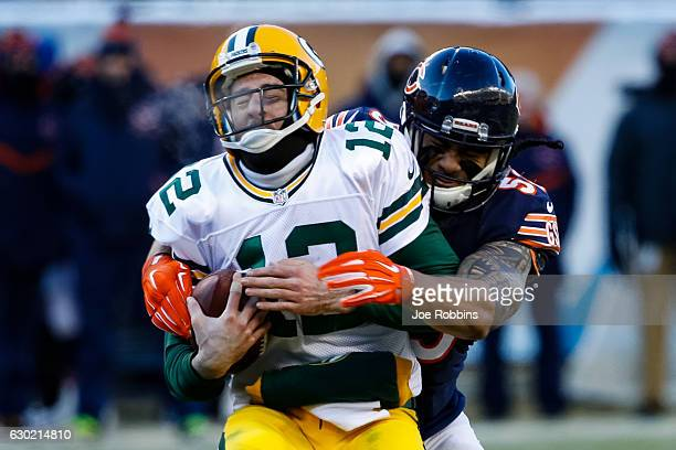 Quarterback Aaron Rodgers of the Green Bay Packers is sacked by John Timu of the Chicago Bears in the fourth quarter at Soldier Field on December 18...