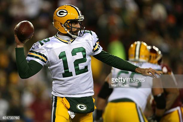 Quarterback Aaron Rodgers of the Green Bay Packers passes the ball while teammate guard Lane Taylor blocks against the Washington Redskins in the...