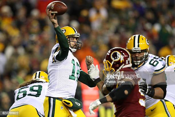 Quarterback Aaron Rodgers of the Green Bay Packers passes the ball while teammate guard Lane Taylor blocks against outside linebacker Ryan Kerrigan...