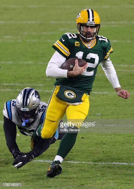 Quarterback Aaron Rodgers of the Green Bay Packers runs against defensive end Brian Burns of the Carolina Panthers during the game at Lambeau Field...