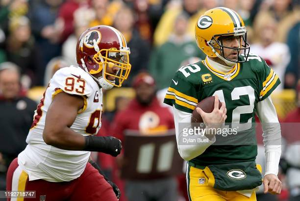 Quarterback Aaron Rodgers of the Green Bay Packers scrambles against defensive end Jonathan Allen of the Washington Redskins during the game at...