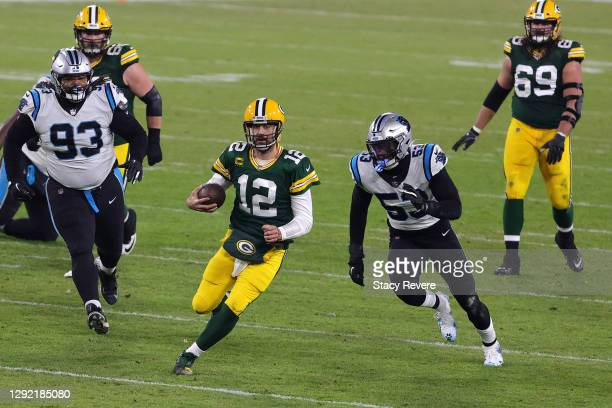 Quarterback Aaron Rodgers of the Green Bay Packers scrambles against the defensive end Brian Burns of the Carolina Panthers second half of the game...