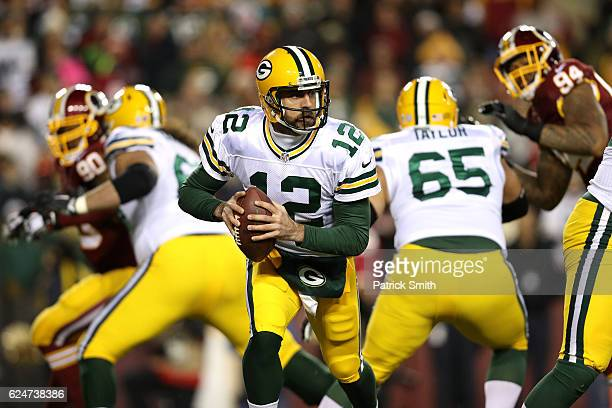 Quarterback Aaron Rodgers of the Green Bay Packers scrambles while teammates guard Lane Taylor and tackle David Bakhtiari block against the...