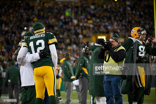 Quarterback Aaron Rodgers of the Green Bay Packers takes a moment to take a photo during the game against the Minnesota Vikings at Lambeau Field on...