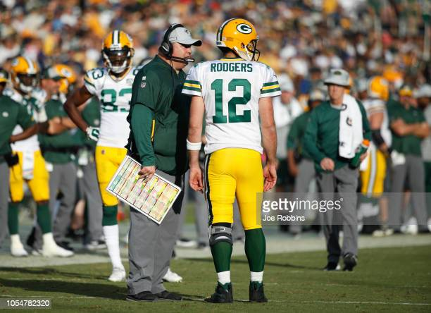 Quarterback Aaron Rodgers of the Green Bay Packers talks with head coach Mike McCarthy during the game against the Los Angeles Rams at Los Angeles...