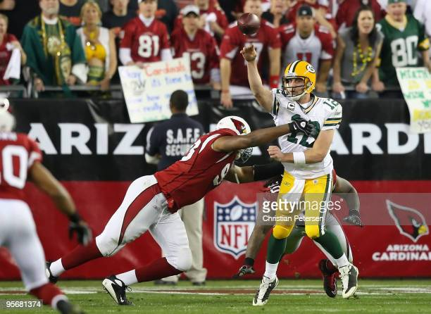 Quarterback Aaron Rodgers of the Green Bay Packers throws a pass under pressure from Calais Campbell of the Arizona Cardinals during overtime of the...