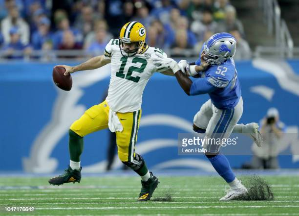 Quarterback Aaron Rodgers of the Green Bay Packers tries to avoid a tackle by Christian Jones of the Detroit Lions during the first half at Ford...