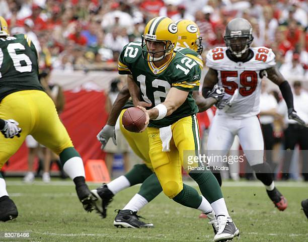 Quarterback Aaron Rogers of the Green Bay Packers hands off during a NFL game against the Tampa Bay Buccaneers at Raymond James Stadium on September...