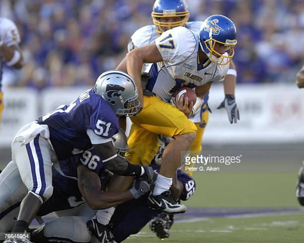 Quarterback Adam Tafralis of the San Jose State Spartans tries to brake away from defenders Justin Roland and Moses Manu of the Kansas State Wildcats...