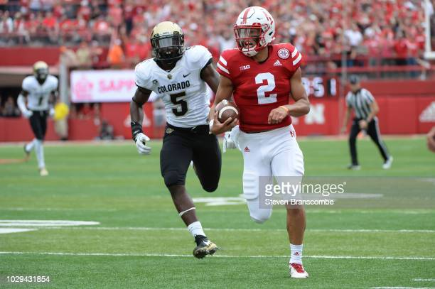 Quarterback Adrian Martinez of the Nebraska Cornhuskers outruns linebacker Davion Taylor of the Colorado Buffaloes to score in the first half at...