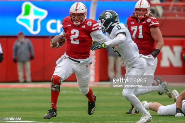 Quarterback Adrian Martinez of the Nebraska Cornhuskers runs against safety David Dowell of the Michigan State Spartans in the first half at Memorial...