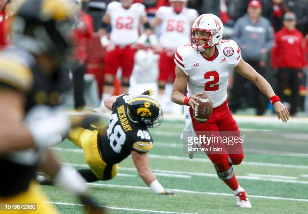Quarterback Adrian Martinez of the Nebraska Cornhuskers scrambles in the first half in front of linebacker Jack Hockaday of the Iowa Hawkeyes on...