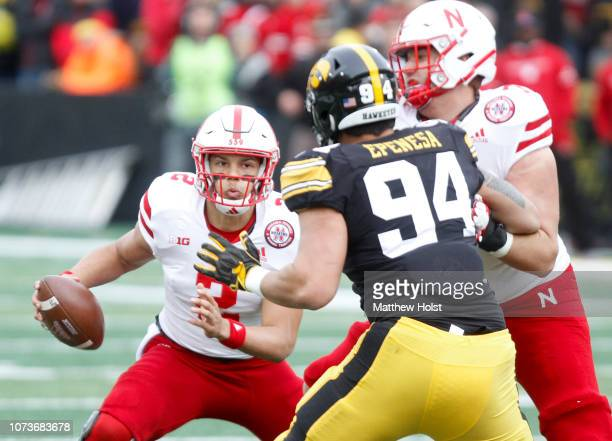 Quarterback Adrian Martinez of the Nebraska Cornhuskers scrambles in the first half in front of defensive end AJ Epenesa of the Iowa Hawkeyes on...
