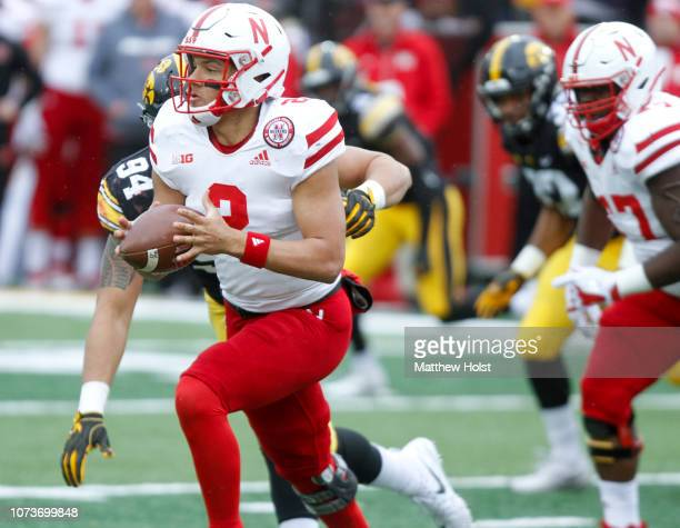 Quarterback Adrian Martinez of the Nebraska Cornhuskers scrambles in the second half in front of defensive end AJ Epenesa of the Iowa Hawkeyes on...