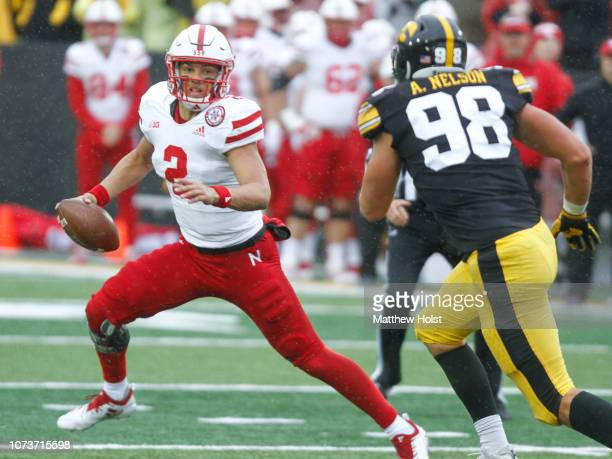 Quarterback Adrian Martinez of the Nebraska Cornhuskers scrambles in the second half in front of defensive end Anthony Nelson of the Iowa Hawkeyes on...
