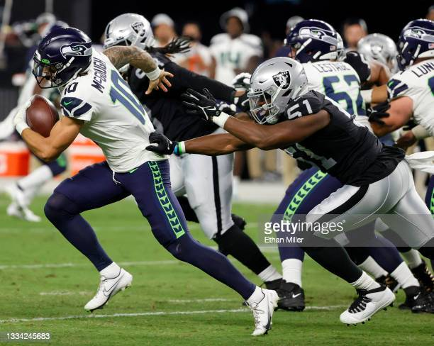 Quarterback Alex McGough of the Seattle Seahawks rushes for a first down against defensive end Malcolm Koonce of the Las Vegas Raiders during a...