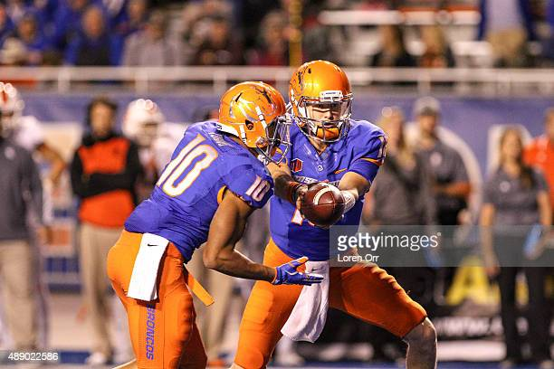 Quarterback Alex Ogle of the Boise State Broncos hands off to running back Cory Young during second half action against the Idaho State Bengals on...