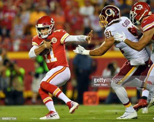 Quarterback Alex Smith of the Kansas City Chiefs is chased by outside linebacker Ryan Kerrigan of the Washington Redskins during the game at...