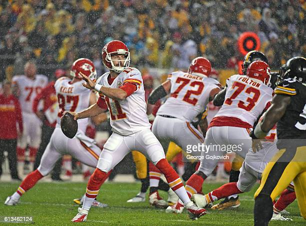 Quarterback Alex Smith of the Kansas City Chiefs passes behind the blocking of tight end Travis Kelce tackle Eric Fisher and guard Zach Fulton as...