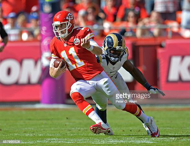 Quarterback Alex Smith of the Kansas City Chiefs rushes past defensive end Robert Quinn of the St Louis Rams during the first half on October 26 2014...