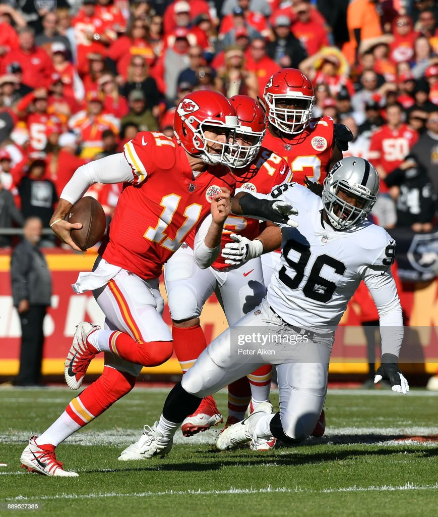 Quarterback Alex Smith #11 of the Kansas City Chiefs scrambles past defensive end Denico Autry #96 of the Oakland Raiders during the game at Arrowhead Stadium on December 10, 2017 in Kansas City, Missouri.