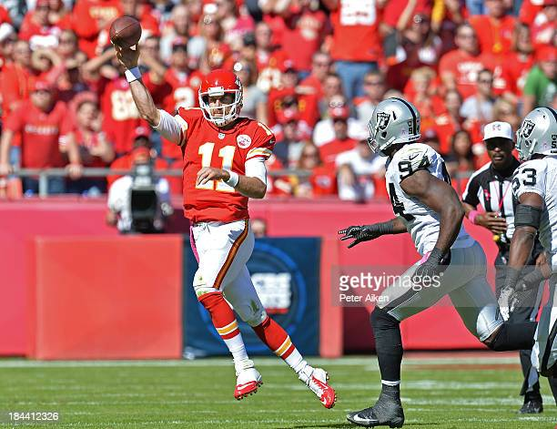Quarterback Alex Smith of the Kansas City Chiefs throws a pass down field under pressure from linebacker Kevin Burnett of the Oakland Raiders during...