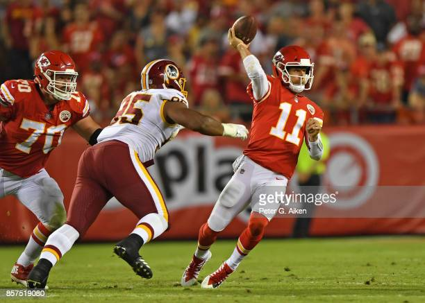 Quarterback Alex Smith of the Kansas City Chiefs throws a pass against pressure from defensive linemen Jonathan Allen of the Washington Redskins...
