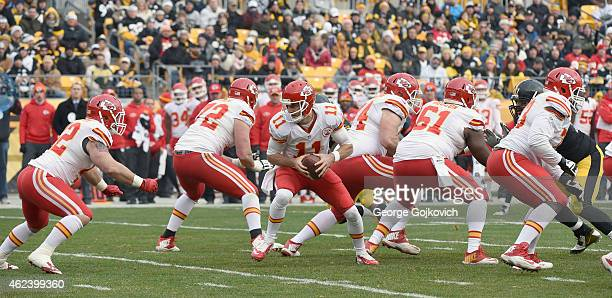 Quarterback Alex Smith of the Kansas City Chiefs turns to hand off to fullback Anthony Sherman as offensive linemen Eric Fisher Jeff Linkenbach...