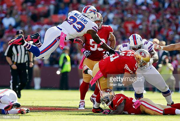 Quarterback Alex Smith of the San Francisco 49ers runs for a first down as cornerback Aaron Williams of the Buffalo Bills flies in on the tackle in...