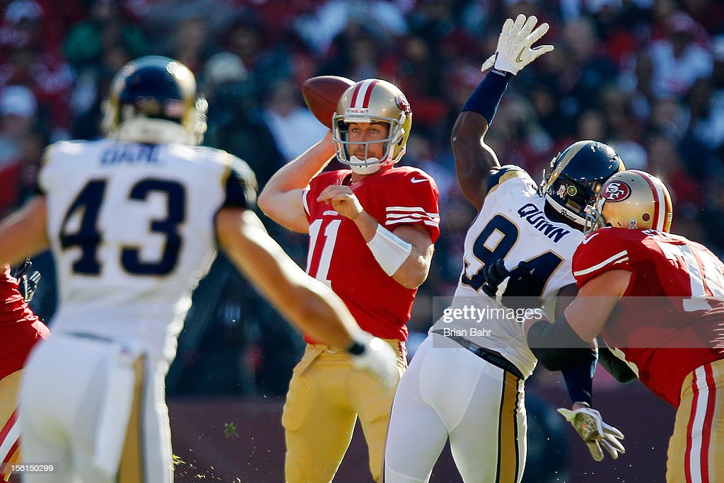 Quarterback Alex Smith #11 of the San Francisco 49ers throws under pressure from defensive end Robert Quinn #94 of the St. Louis Rams in the first half on November 11, 2012 at Candlestick Park in San Francisco, California. The teams tied 24-24 in overtime.