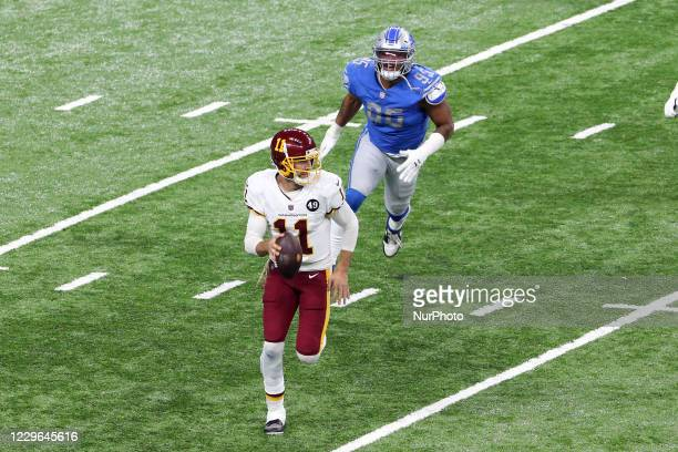 Quarterback Alex Smith of the Washington Football Team carries the ball while looking for an opportunity to pass under the pressure of defensive end...