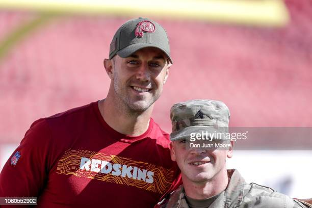 Quarterback Alex Smith of the Washington Redskins pose with an military servicemen before the game against the Tampa Bay Buccaneers at Raymond James...