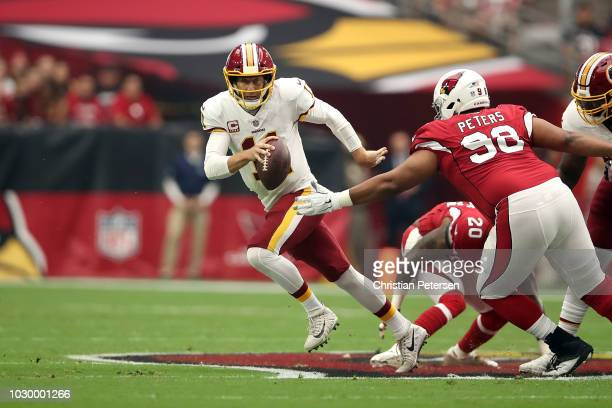 Quarterback Alex Smith of the Washington Redskins runs past defensive tackle Corey Peters of the Arizona Cardinals during the first quarter at State...