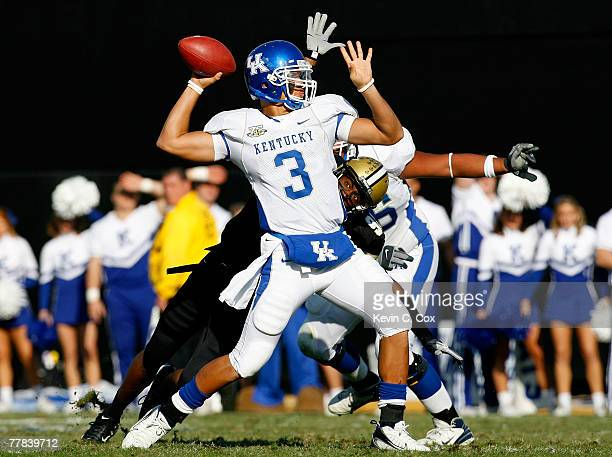 Quarterback Andre Woodson of the Kentucky Wildcats passes for a touchdown while being pressured by defensive end Broderick Stewart of the Vanderbilt...