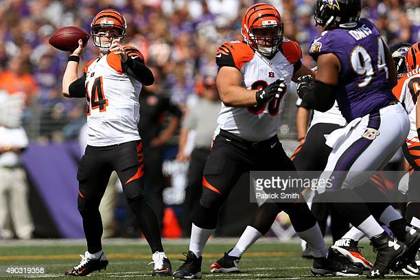 Quarterback Andy Dalton of the Cincinnati Bengals drops back to throw while guard Kevin Zeitler of the Cincinnati Bengals works against defensive...