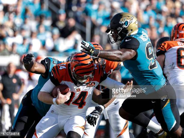 Quarterback Andy Dalton of the Cincinnati Bengals is sacked by Defensive Ends Yannick Ngakoue and Calais Campbell of the Jacksonville Jaguars during...