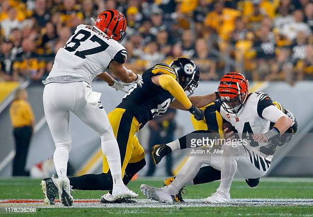Quarterback Andy Dalton of the Cincinnati Bengals is tackled by the defense of the Pittsburgh Steelers during the game at Heinz Field on September 30...