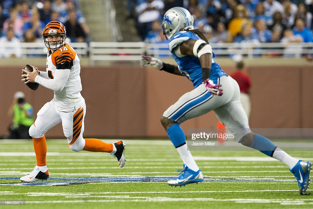 Quarterback Andy Dalton #14 of the Cincinnati Bengals scrambles out of the pocket while under pressure from defensive end Willie Young #79 of the Detroit Lions during the second half at Ford Field on October 20, 2013 in Detroit, Michigan. The Bengals defeated the Lions 27-24.