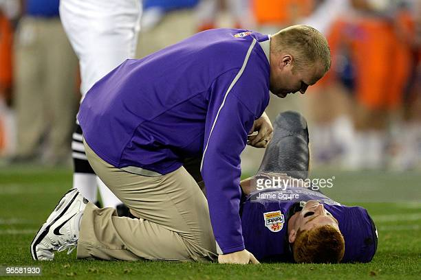 Quarterback Andy Dalton of the TCU Horned Frogs lays on the ground injured as he is getting checked on by a trainer after getting sacked against the...