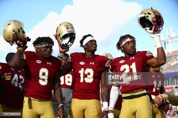 Quarterback Anthony Brown Lukas Denis and Kobay White of the Boston College Eagles celebrate after the victory over the Louisville Cardinals at...