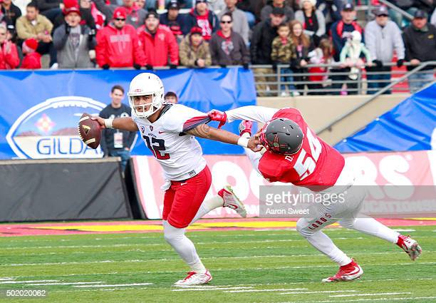 Quarterback Anu Solomon of the Arizona Wildcats breaks a tackle from linebacker Donnie White of the New Mexico Lobos in the first half of the game...