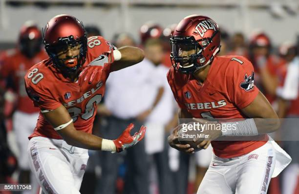 Quarterback Armani Rogers of the UNLV Rebels fakes a handoff to wide receiver Brandon Presley during their game against the San Jose State Spartans...