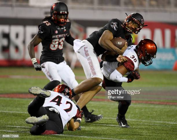 Quarterback Armani Rogers of the UNLV Rebels is tackled by linebacker Troy Cassidy and fullback Adam Eastwood of the San Diego State Aztecs during...
