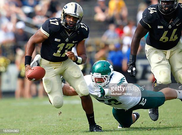 Quarterback Austin Parker of the Purdue Boilermakers runs away from the tackle of defensive lineman Pat O'Connor of the Eastern Michigan Eagles at...