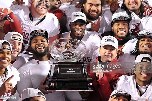 Quarterback Baker Mayfield linebacker Eric Striker and head coach Bob Stoops of the Oklahoma Sooners pose with the Big XII Championship trophy after...
