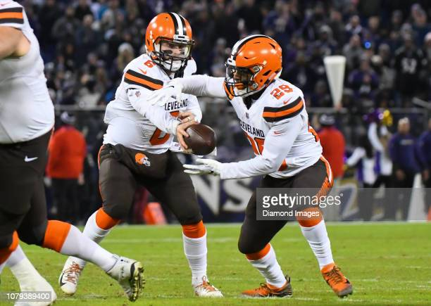 Quarterback Baker Mayfield of the Cleveland Browns hands the ball to running back Duke Johnson in the fourth quarter of a game against the Baltimore...